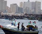 People watch as Palestinians prepare to sail a boat towards Europe aiming to break Israel's blockade on Gaza, at the sea in Gaza May 29, 2018.