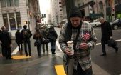 A homeless man begs for money with a U.S. flag and an empty coffee cup in San Francisco, California.