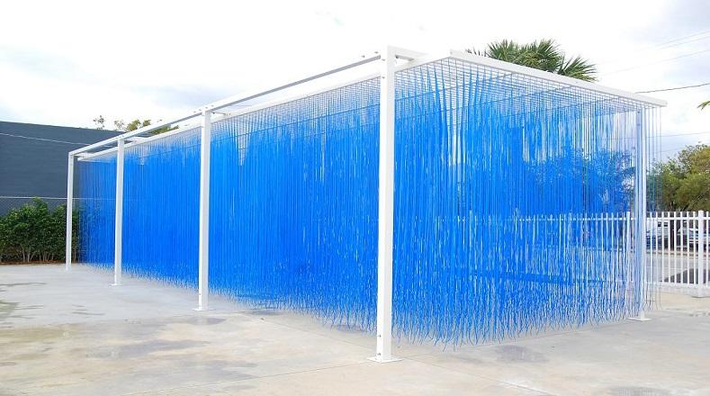 """Esta obra denominada """"Penetrable Azul"""", permite al espectador vivir una experiencia óptica y táctil. Al ser penetrada puedes sentir la lluvia de cuerditas por todo el cuerpo mientras las palpa."""