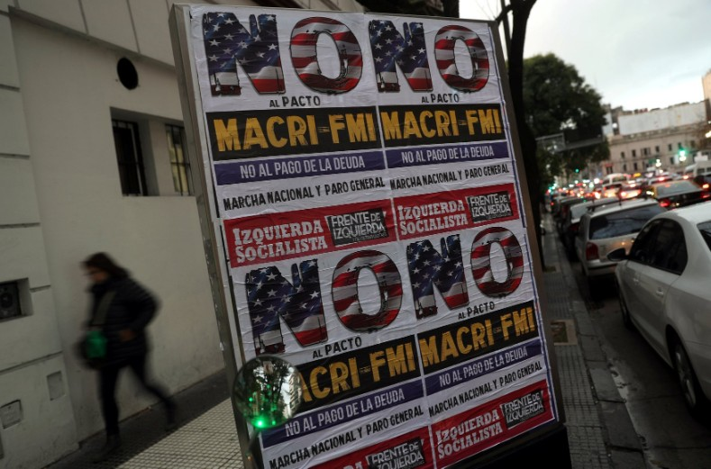 "A woman walks behind posters that read ""No to the Macri-IMF pact"" in Buenos Aires."