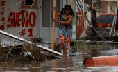 A woman tries to walk out from her house after it was hit by Hurricane Maria in Salinas, Puerto Rico, September 21, 2017.