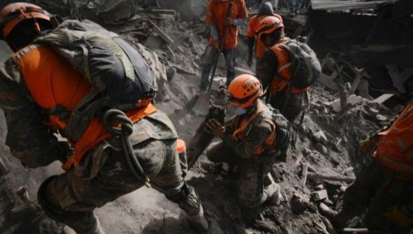 Soldiers search for remains at an area affected by the eruption of El Fuego volcano in Guatemala.