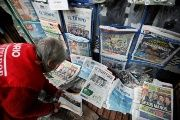 A woman sells newspapers that show candidates Gustavo Petro and Ivan Duque go to the second round of presidential election, in Bogota, Colombia May 28, 2018.