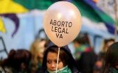 "A demonstrator holds a baloon that reads ""Legal abortion now"" during a protest against femicides and violence against women in Buenos Aires, Argentina, June 4, 2018."