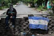 A man holding a homemade mortar sits on a roadblock in Managua, Nicaragua June 16, 2018.