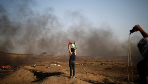 A demonstrator gestures during a protest where Palestinians demand the right to return to their homeland, at the Israel-Gaza border, east of Gaza City May 18, 2018.