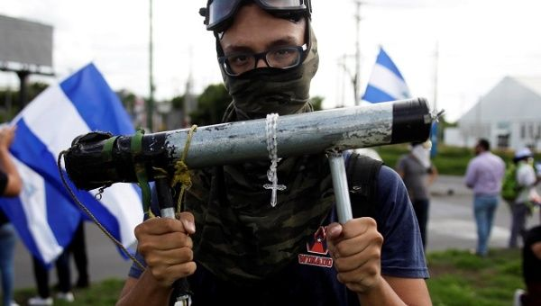 A demonstrator holds a homemade mortar during a protest against the government of Nicaragua
