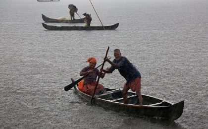 A fisherman and his wife row their boat in a fish farm as it rains heavily on the outskirts of Kochi, India, May 2018.