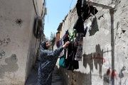 A Palestinian woman hangs laundry outside her house at Khan Younis refugee camp in the southern Gaza Strip June 20, 2018.