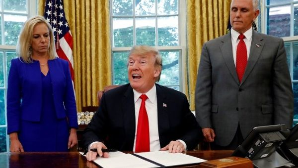 U.S. President Donald Trump (C) signs an executive order to keep migrant families together as they enter the United States.
