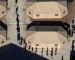 Immigrant children are led by staff in single file between tents at a U.S. detention facility.