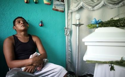 Nelson Gabriel Lorio Sandoval sits next to the coffin of his one-year-old son, Teyler, killed by a stray bullet in Managua.