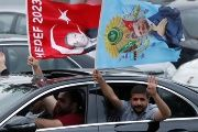 Supporters of Turkish President Tayyip Erdogan hold up his flags front of a Turkish flag in front of Turkey's ruling AK Party (AKP) headquarters in Istanbul,Turkey, June 24, 2018.