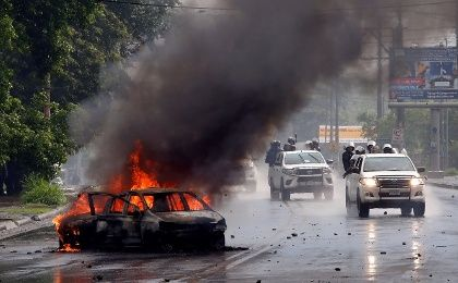 Riot police officers travel past a burning car during clashes with the anti-government protesters in Managua, Nicaragua May 28, 2018.