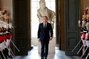 French President Emmanuel Macron walks through the Galerie des Bustes (Busts Gallery) to access the Versailles Palace's hemicycle.