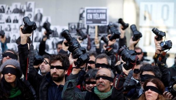 Blindfolded journalists protest the layoff of 300 workers of Argentina