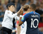 One photograph on social media showed one of the pitch invaders, a woman with blonde hair tucked under a police cap, performing a high-five with France player Kylian Mbappe before being caught.