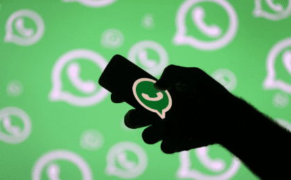 FILE PHOTO: A man poses with a smartphone in front of displayed Whatsapp logo in this illustration September 14, 2017.