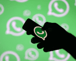 A man poses with a smartphone in front of displayed Whatsapp logo in this illustration Sept. 14, 2017.
