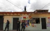 Police officers stand guard on a street while colleagues help an elderly couple move their belongings in Tegucigalpa, Honduras August 10, 2014.