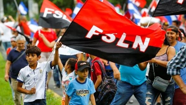 People hold Sandinista National Liberation Front flags on the 39th anniversary of the revolution.