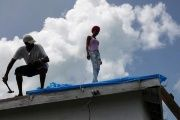Devon Warner and his daughter Che Niesha work on the roof in Barbuda.