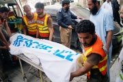 Rescue workers move the body of Ikramullah Gandapur, a candidate of the Pakistan Tehreek-e-Insaf (PTI), or Pakistan Justice Movement.