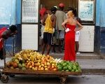 A man pushes a cart with fruits in front of a shop, as a picture of the former Cuban President Raul Castro is seen on the wall, in Havana, Cuba July 21, 2018.