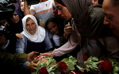 Relatives mourn as they look at the body of Palestinian teenager Arkan Mezeher, who was killed by Israeli soldiers.