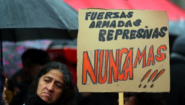 """A woman holds a sign that reads """"Repressive armed forces, never again"""" in to protest of Macri government"""