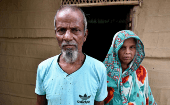 Abdul Suban and his wife pose for a photograph outside their home in Nellie village, in Morigaon district, in the northeastern state of Assam, India July 25, 2018.