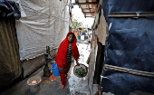 A woman from the Rohingya community carries vegetables in a camp in Delhi, Aug. 17, 2017.