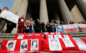 Human rights activists with images of missing people take part in a protest against the decision of the Supreme Court to grant parole to human right abusers during the Chilean dictatorship, in Valparaiso.