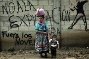 A Mayan indigenous woman and her son in front of a graffiti that reads