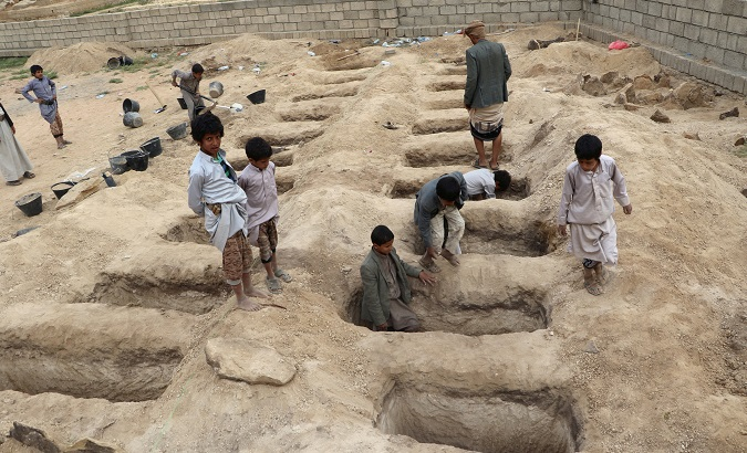 Boys inspect graves prepared for victims of Thursday's air strike in Saada province, Yemen.