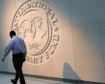 A person walks past the International Monetary Fund (IMF) logo at its headquarters in Washington, U.S., May 10, 2018.