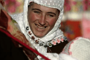 A Bulgarian Muslim woman smiles as she plays with a baby during a wedding ceremony in the village of Ribnovo, in the Rhodope Mountains, November 19, 2006 .