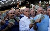 People holding U.S. dollars stand in front of a currency exchange office after Erdogan's call to sell dollar savings to support the lira, in Ankara, Turkey Aug.14, 2018.