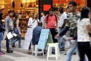 People look at lists of job openings posted on a street in downtown Sao Paulo, Brazil.