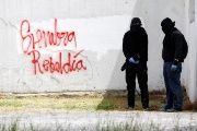 Demonstrators by graffiti that reads 'sowing rebellion' in an anti-government protest at the National University in Bogota, Colombia.