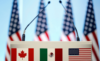 The flags of Canada, Mexico and the U.S. on a lectern before a joint news conference on the closing of the seventh round of NAFTA talks in Mexico City, Mexico, March 5, 2018