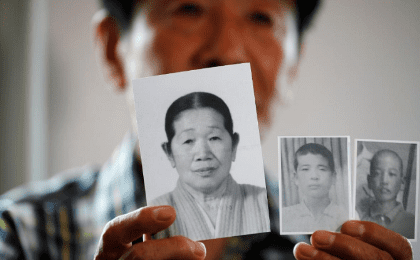 A man selected as a participant for a reunion shows pictures of his deceased mother and little brothers living in North Korea, at a hotel used as a waiting place in Sokcho, South Korea, August 19, 2018.