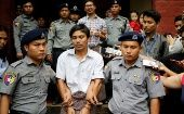 Detained Reuters journalist Kyaw Soe Oo is escorted by police after a court hearing in Yangon, Myanmar, August 20, 2018.