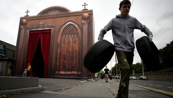 Boys carry tyres past a drive-thru confession box, set up beside Phoenix Park, ahead of the visit of Pope Francis to Dublin, Ireland, August 20, 2018.