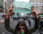 Abortion rights activists holds a sign during a gathering as lawmakers are expected to vote on a bill legalizing abortion, in Buenos Aires, Argentina August 8, 2018. The sign reads