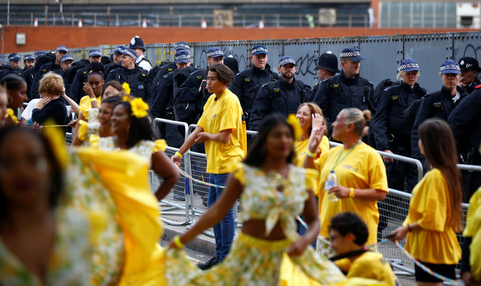 Police officers look on as revellers take part in the Notting Hill Carnival