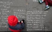 A child writes with chalk as people take part in a protest during the visit of Pope Francis to Dublin, Ireland, August 26, 2018.
