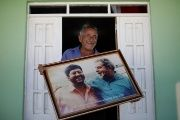 Antonio Ferreira, a cousin of ex-Brazilian President Luiz Inacio Lula da Silva holds a picture of Lula with the former mayor of Caetes at his home in Caetes, Brazil.