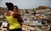 Ysamar Figueroa, carrying her son, looks at the damage after Hurricane Maria in Canovanas, Puerto Rico, September, 2017.