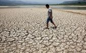 A man walks along the dried-up bed of a reservoir in Sanyuan county, in China